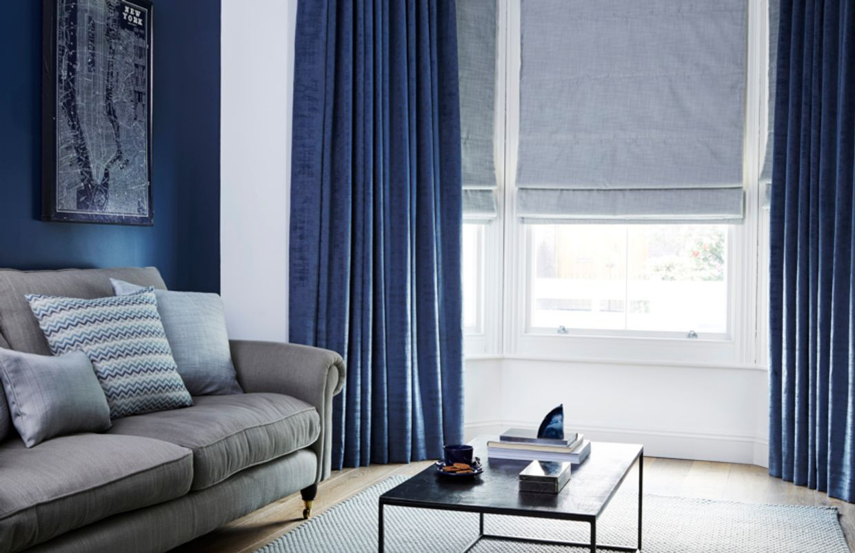 stylish blue curtains paired with grey roman blinds in a living room bay window
