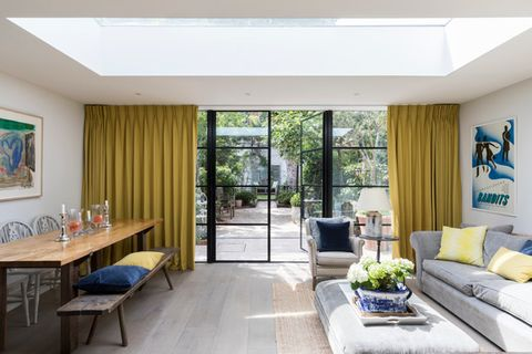 Yellow curtains fitted to a wide door windows that open onto a patio in a kitchen featuring a dining table and sofa