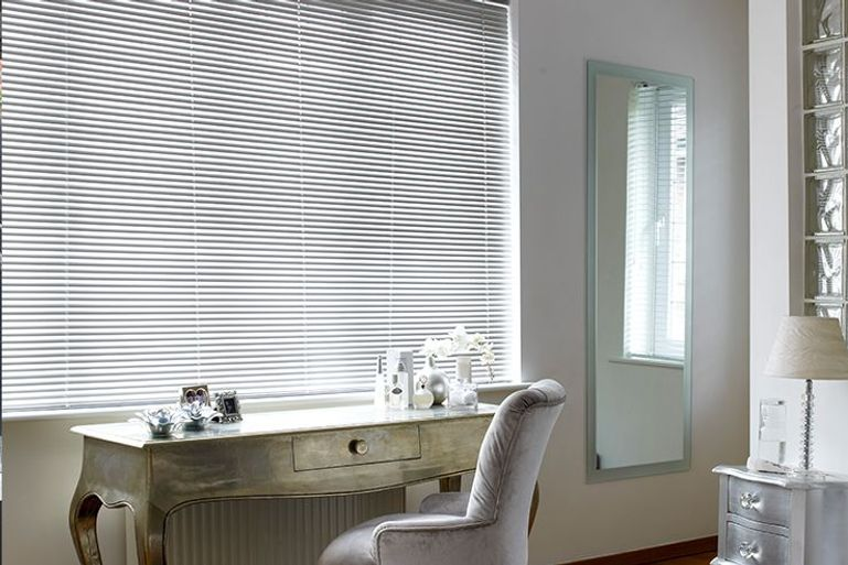 dressing table in front of large window with white venetian blinds