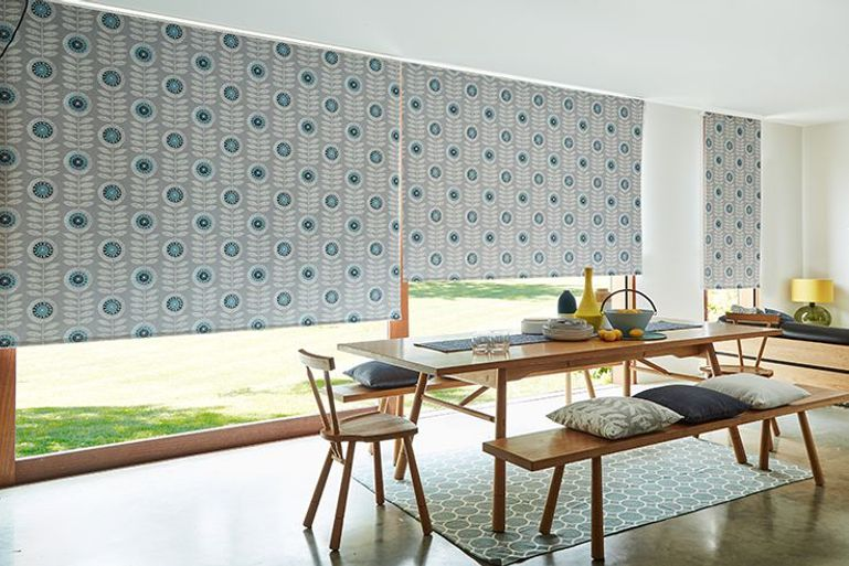 Dining room with a large table in front of floor to ceiling windows fitted with Neisha Teal Roller Blinds
