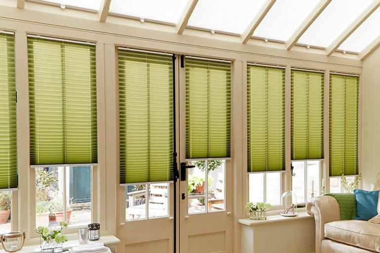 Green pleated blinds hung in conservatory