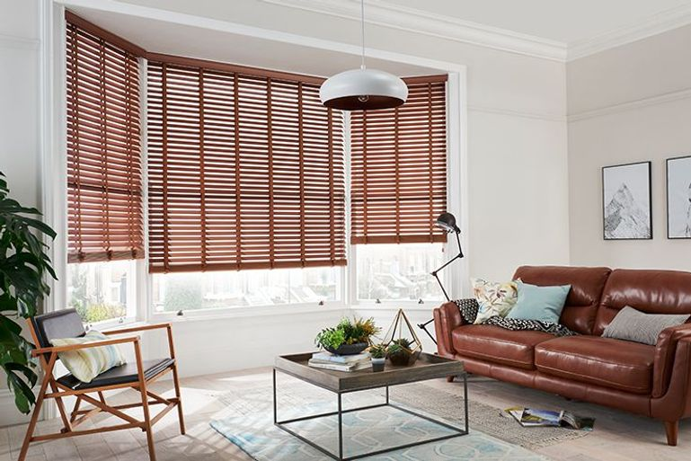 brown wooden Venetian blinds in a contemporary living room bay window
