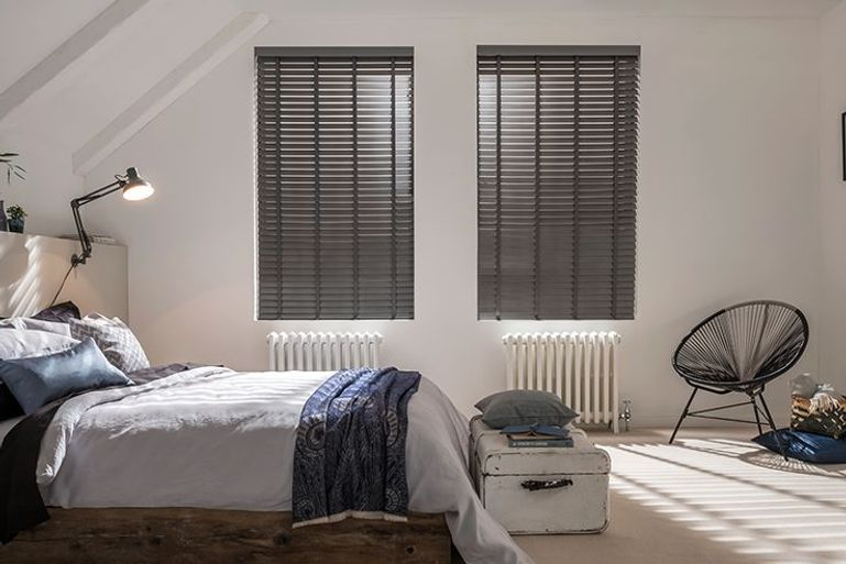grey faux wooden venetian blinds in a minimalist bedroom window