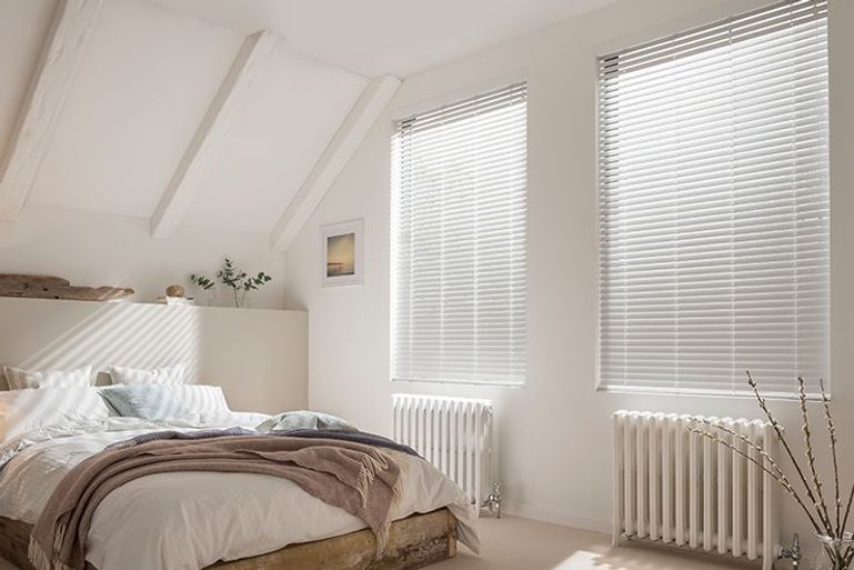 faux wood white Venetian blinds in a bedroom window
