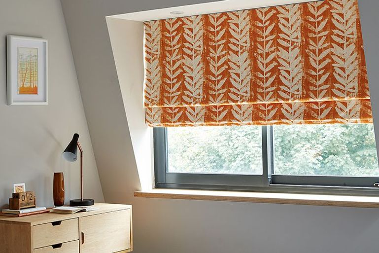 orange patterned roman blind in a bedroom window