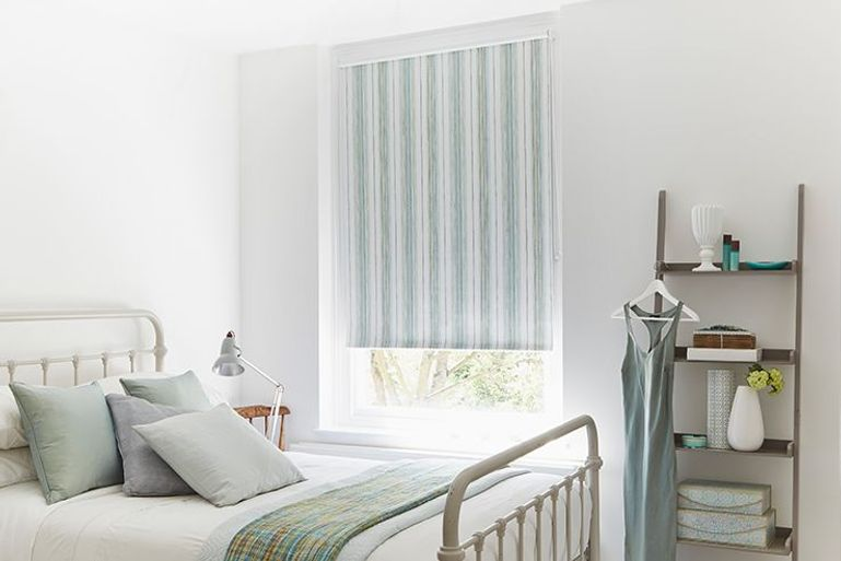 green and white striped roller blinds in a bedroom window