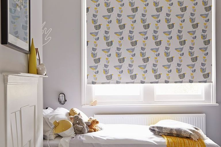 white with grey and yellow bird print roller blinds in a bedroom window