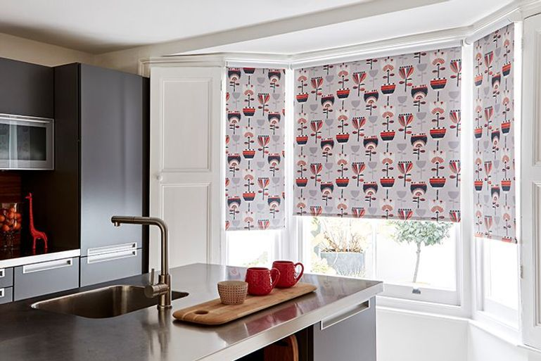 white kitchen roman blinds with flower print in a kitchen window