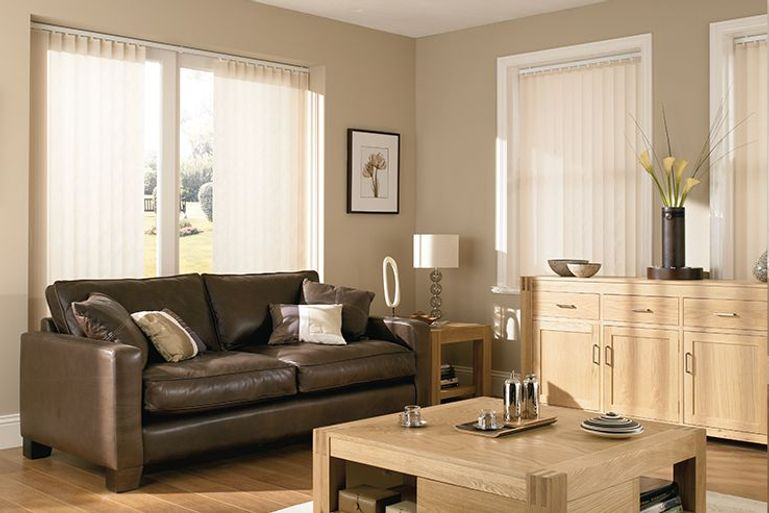 living room with plain white vertical blinds and a brown leather sofa