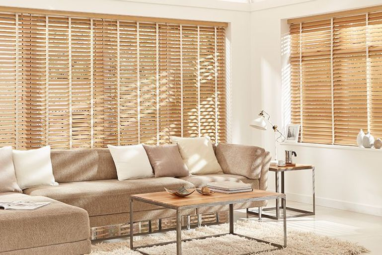 plain white living room with natural wooden venetian blinds in the window