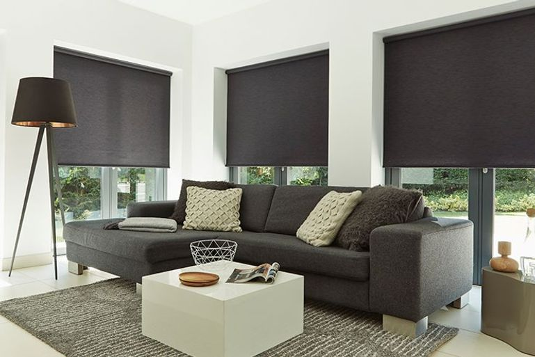 black roller blinds in large living room windows
