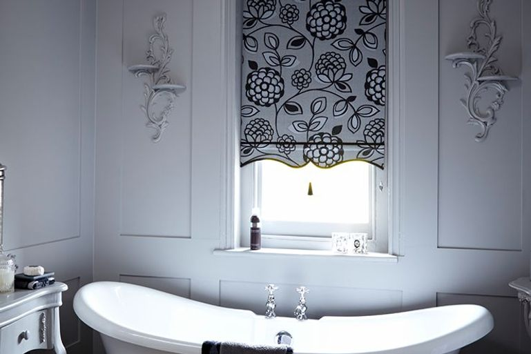 black patterned roller blinds in a bathroom window