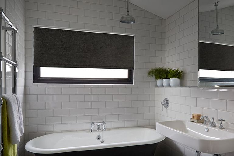 wide black roller blind in a modern bathroom window
