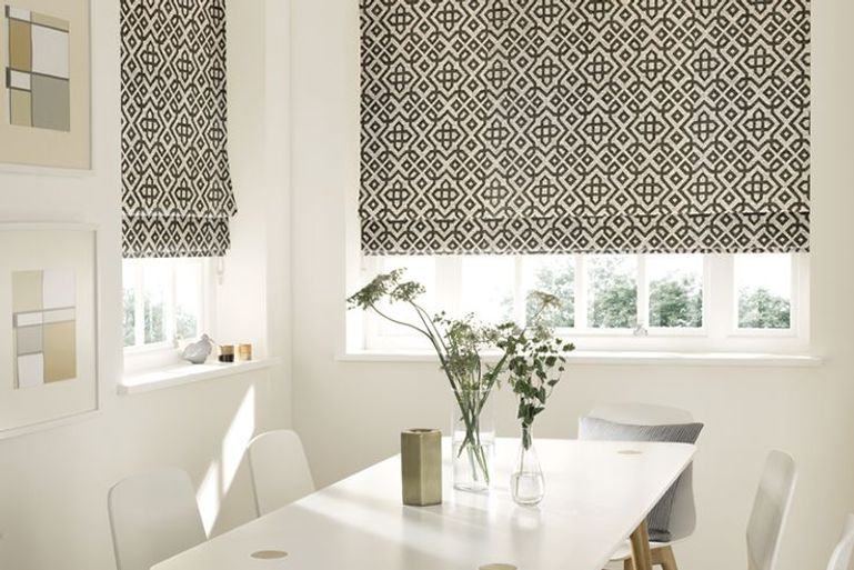 black and white patterned roman blind in dining room window