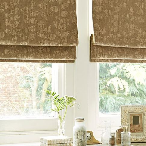 patterned light brown roman blinds in a window