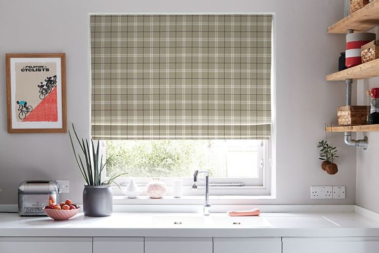 green check roman blinds in a kitchen window behind a sink