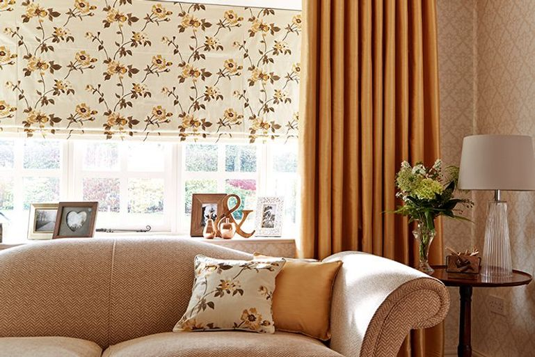 beige blackout roman blinds and curtains with a yellow flower print in a living room window