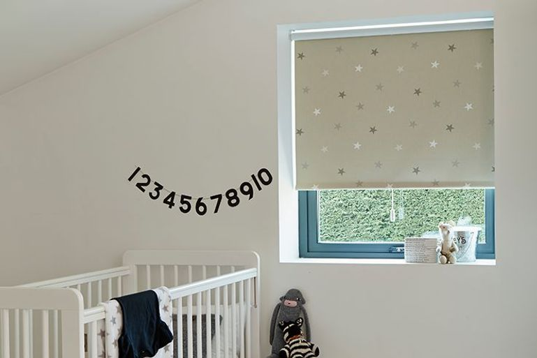 cream blackout roller blinds with stars print in a kids bedroom window