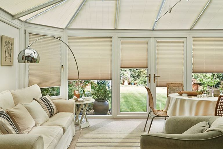 conservatory living room with beige pleated blinds in the windows