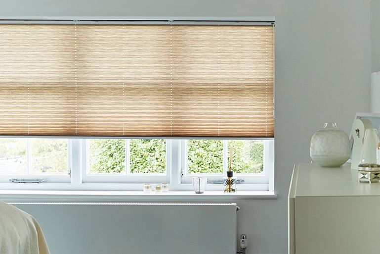 light brown pleated blinds in a bedroom window