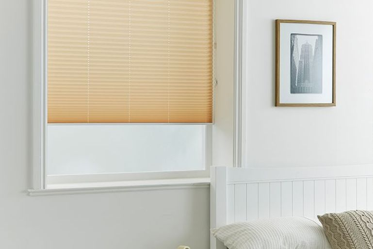 bedroom with cream pleated blinds in the window