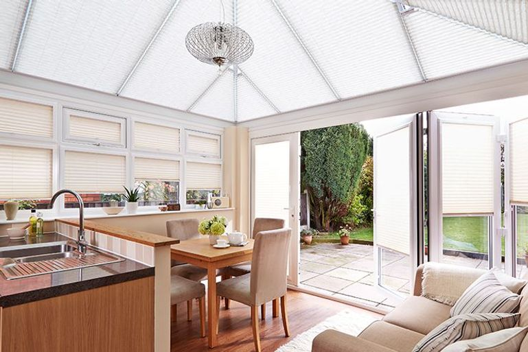 kitchen diner in a conservatory with cream decor and cream pleated blinds