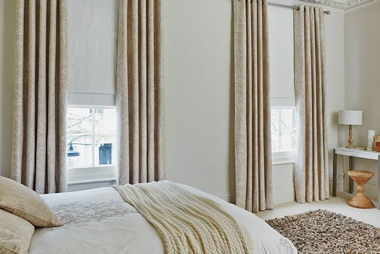 White Roman blinds with cream curtains in a bedroom with 2 windows