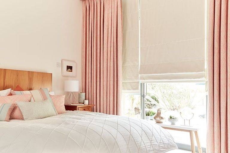 pink curtains with cream roller blinds in a bedroom window