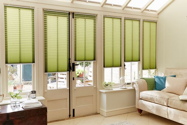 green pleated blinds in a conservatory window