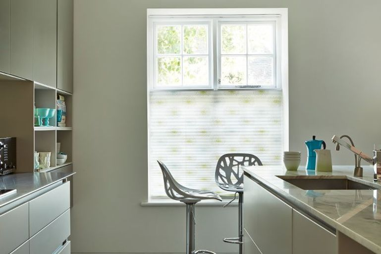 kitchen with white and green pleated blinds in the window