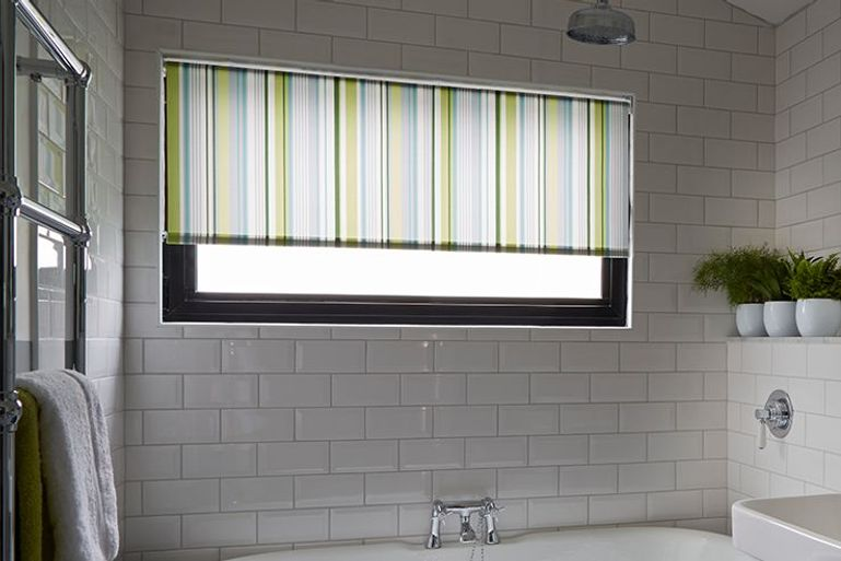 white roller blinds with blue and green stripes in a bathroom window