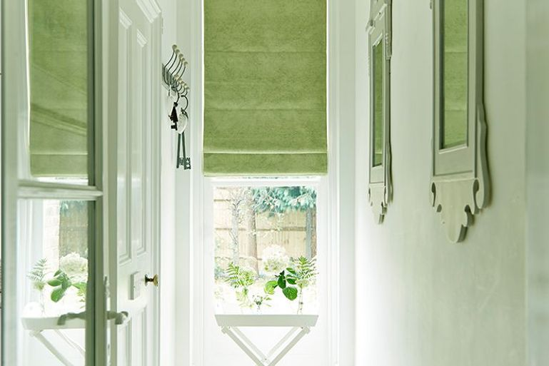 light green roman blinds in a white hallway