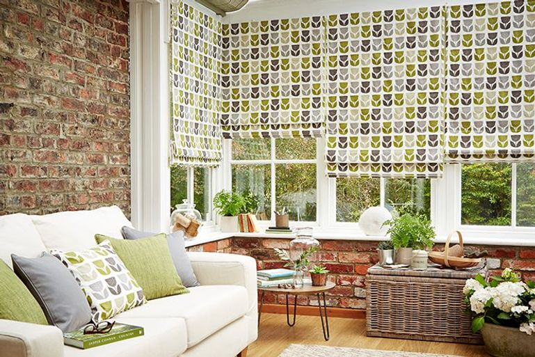 bright green and grey geometrical patterned roman blinds in a conservatory