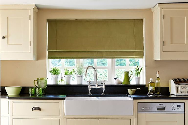 kitchen window with green roman blinds behind a sink and worktop