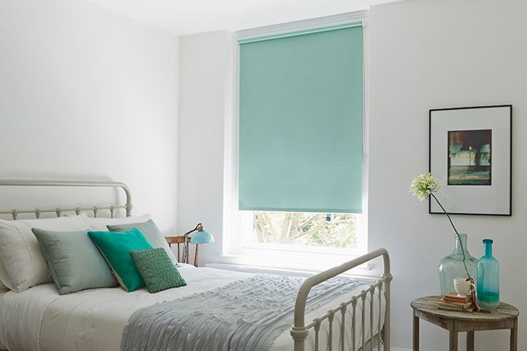 pale blue blackout roller blinds in a bedroom window
