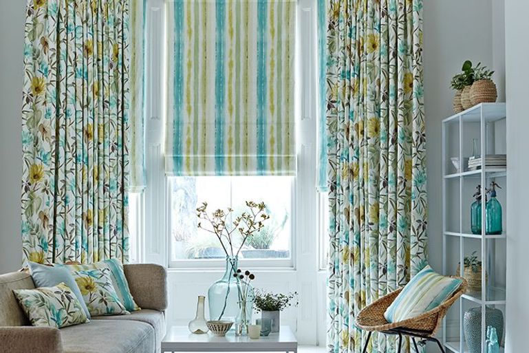 blue and green living room with bright roman blinds and curtains