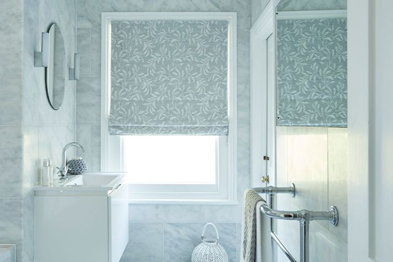 Grey coloured roman blind with silver leaf detail is fitted to a rectangular window in  a bathroom decorated with marble coloured walls and white units