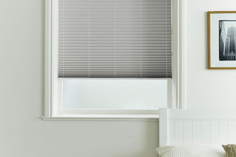 grey pleated blinds in a bedroom window
