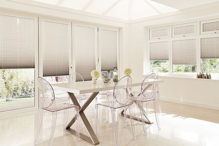 grey pleated blinds in a dining room window