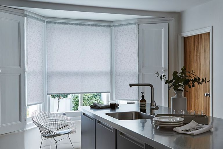 grey roller blinds in a kitchen window