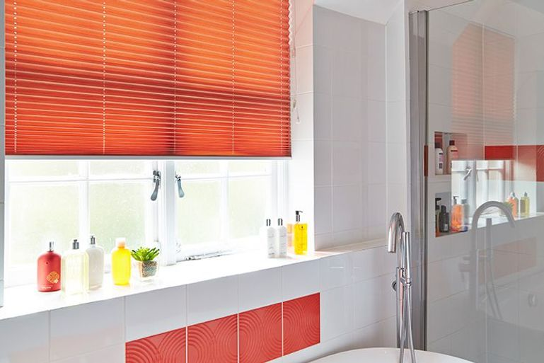 bright orange pleated blinds in a bathroom window