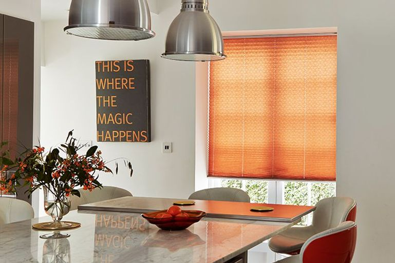 bright orange pleated blind in a modern kitchen dining room window