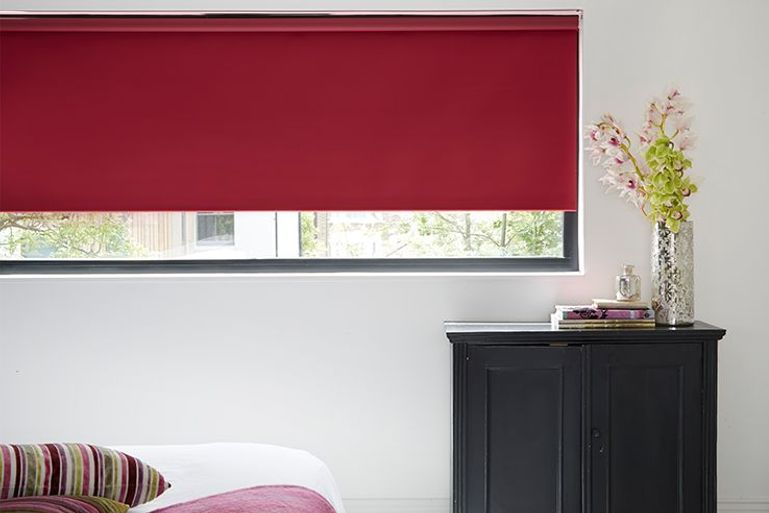 raspberry colour roller blind in a contemporary bedroom window