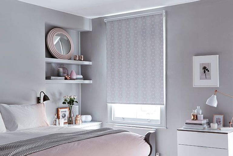 grey roller blinds with light pink triangle details in a bedroom window