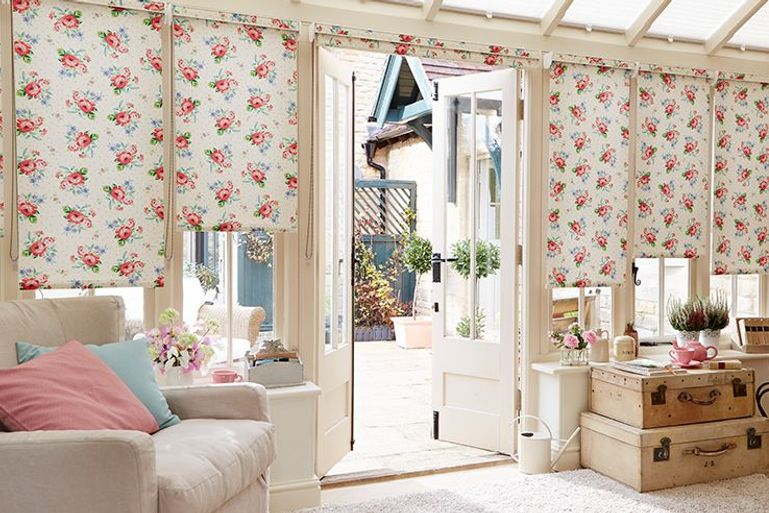 cream roller blinds with pink rose detail pattern in a conservatory window