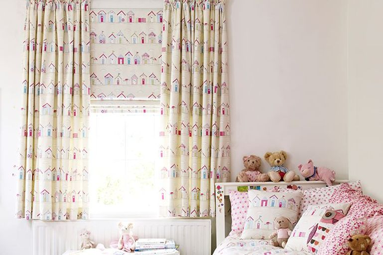 pink patterned blackout roller blinds and curtains with a beach huts design in a child's bedroom