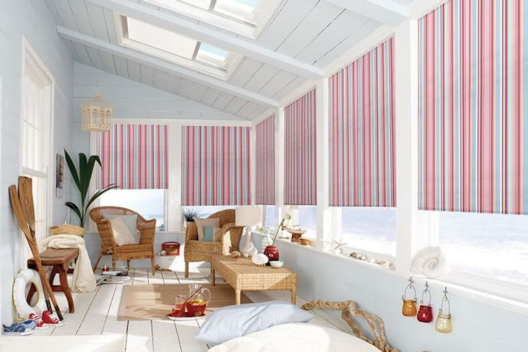pink, red and and blue striped roller blinds in a blackout fabric hanging in a conservatory window