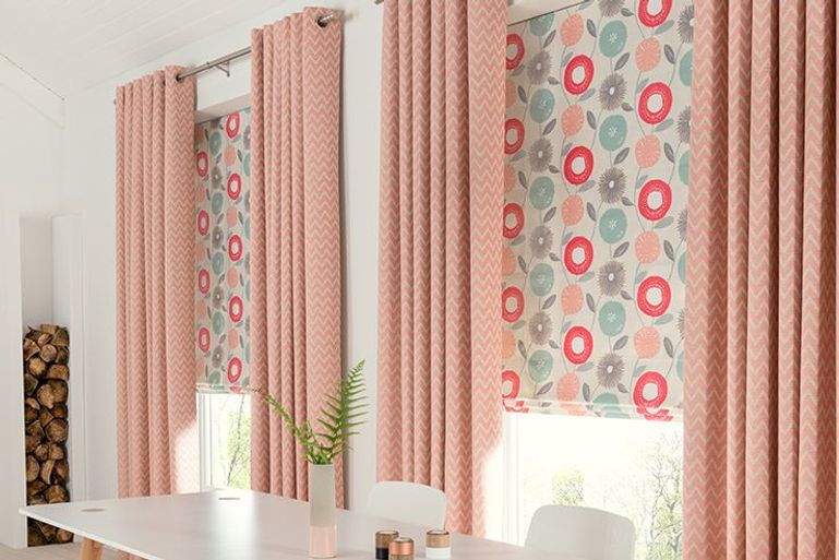 pink blackout curtains and colourful roman blinds in a dining room window