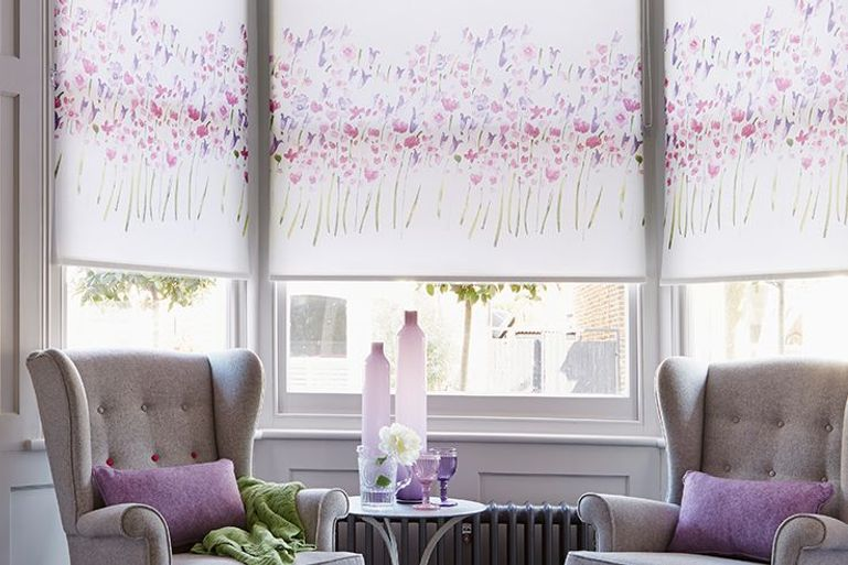 white blinds with purple flower details in a living room window