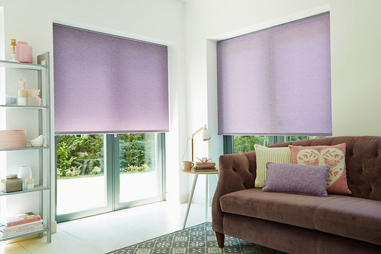purple roller blinds in a modern living room with patio doors